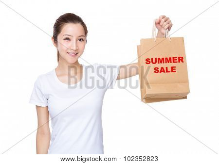 Woman carry with shopping bag and showing phrase of summer sale
