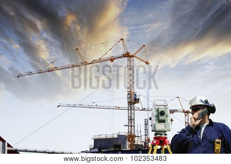surveying engineer with measuring-instrument inside large construction site