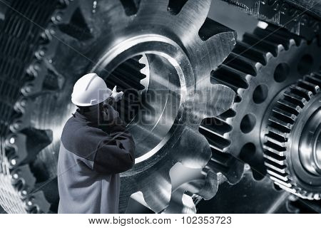 engineer, worker pointing at giant cogwheels and gears machinery, titanium and steel in blue toning .