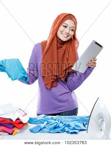Young Woman Wearing Hijab Reading Article On Tablet While Doing Housework