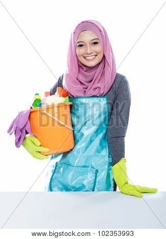 Young Woman Wearing Hijab Holding A Bucket Full Of Cleaning Supplies