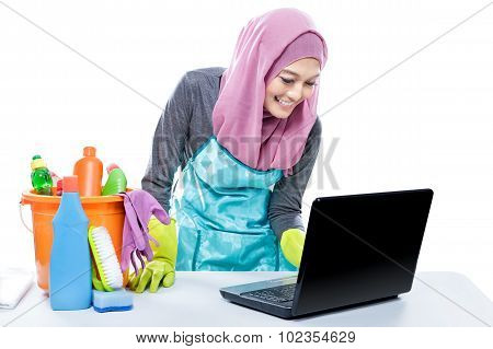 Multitasking Young Housewife Using Laptop While Cleaning Table