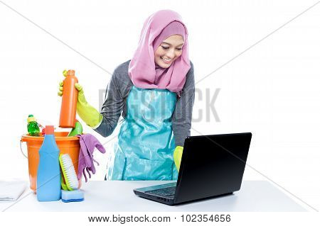 Multitasking Housewife Using Laptop While Cleaning House
