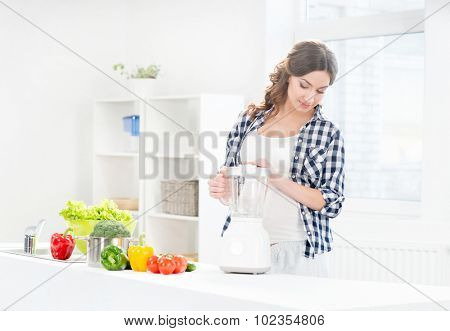 Beautiful pregnant smiling woman cooking with a blender.