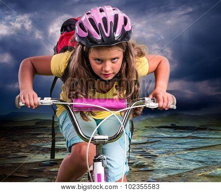 Child girl ride hard on bike to mountain.