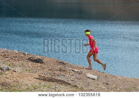 Woman Gets Workout Running Trail Near An Alpine Lake