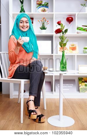Attractive Muslim Woman Sitting And Drining A Cup Of Tea