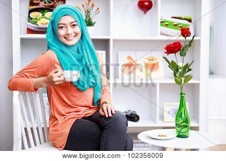 Attractive Muslim Woman Enjoying A Cup Of Tea At Decorated Living Room