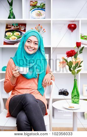 Beautiful Muslim Woman Relax Sitting At Decorated Living Room With A Cup Of Tea