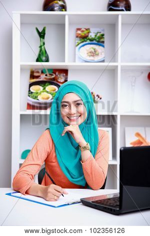 Young Woman Writing An Information From Internet At Office