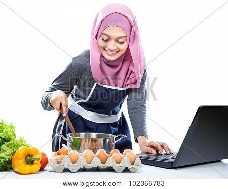 Young Woman Wearing Hijab Cooking With Reference The Laptop