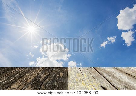 wood floor with sun star and blue sky background.