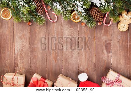 Christmas wooden background with snow fir tree, decor and gift boxes