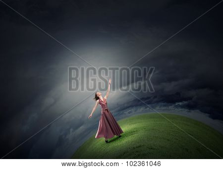Young woman in in dress reaching hand to touch something