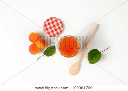 overhead view of jar with fresh apricot jam accompanied by fresh apricots with leaves and wooden spoon