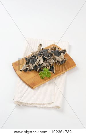 heap of ear mushrooms on wooden cutting board and white place mat