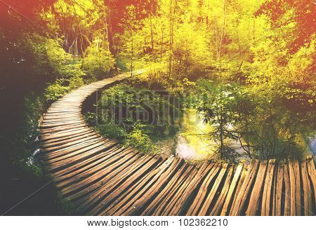 Wooden path and waterfall in Plitvice National Park, Croatia.Filtered image: warm cross processed vintage effect.