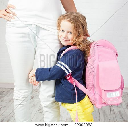 Mother helps her daughter get ready for school. Schoolgirl afraid to go to school