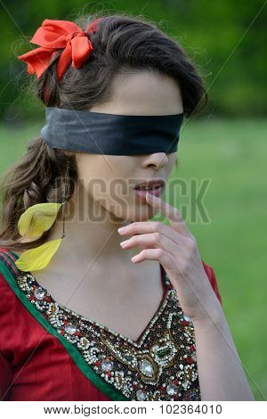 woman with a blindfold on green field