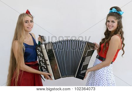 two smiling girls holding old accordion