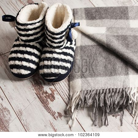 Warm slippers on the background old white floor. Homeliness.