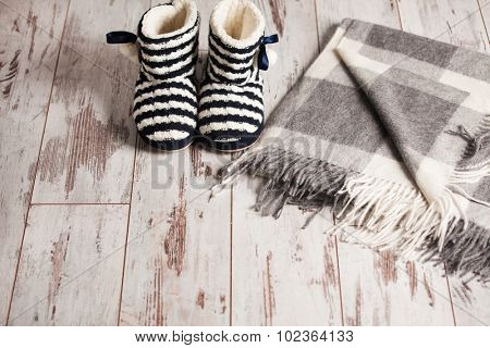 Warm slippers and rug on the background old white floor. Homeliness.