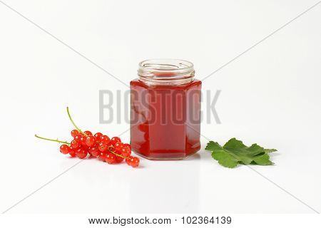opened jar full of red fruit jam accompanied by green leaf and clusters of fresh red currant