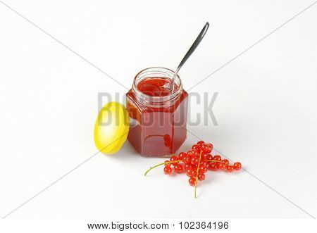 fruit jam in the glass jar with yellow lid, surrounded by fresh clusters of red currant