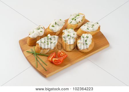 crunchy croutons with chives spread on wooden cutting board