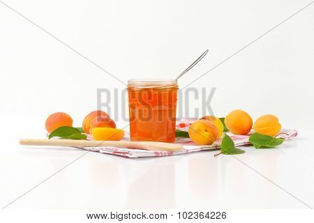 side view of glass jar with apricot jam and immersed spoon, standing on the linen