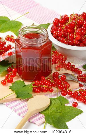 jar with red currant jam surrounded by fresh red currant with leaves