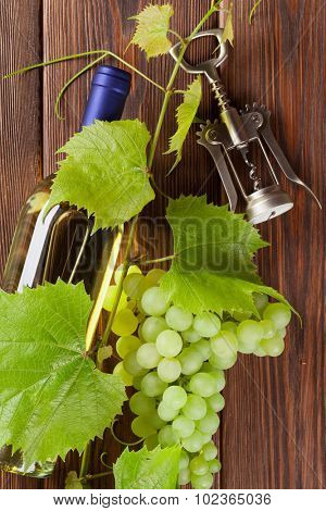 Bunch of grapes, white wine bottle and corkscrew on wooden table background