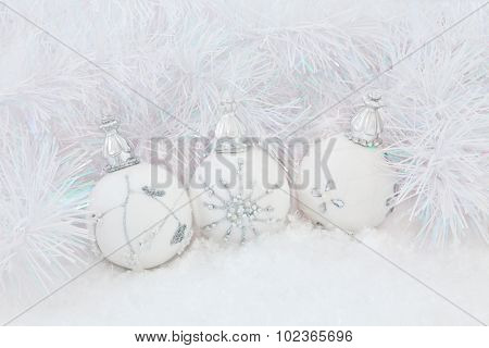 Christmas white bauble decorations on snow with decorative tinsel  background.