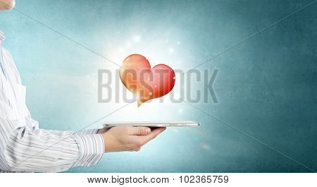 Male hand holding tablet pc with red heart on screen