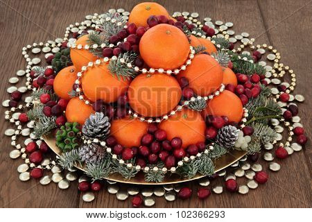 Christmas satsuma orange and cranberry fruit, gold bead and smartie decorations, holly, mistletoe and winter greenery over oak background.