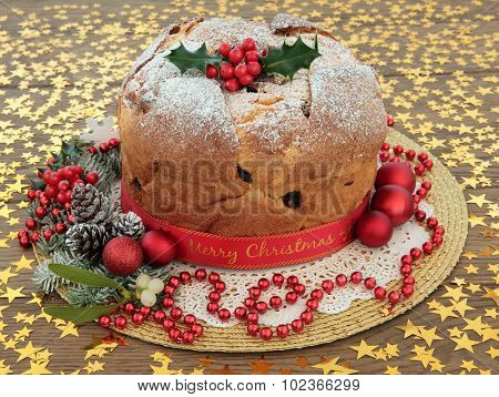 Panettone cake with merry christmas ribbon, holly, mistletoe, decorations and winter greenery over oak background with gold stars.