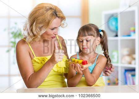 kid girl and mother playing toys at home
