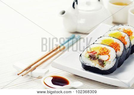 Sushi set, green tea and sakura branch on bamboo mat
