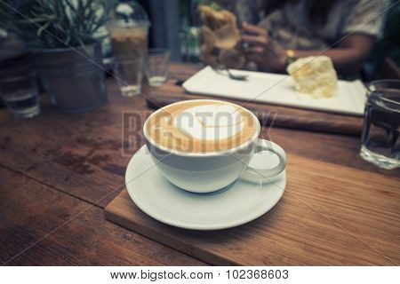 Closeup cup of coffee and women eating cake background.