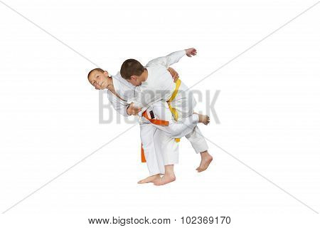 Children in judogi are training judo throws