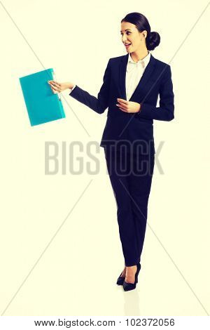 Full length businesswoman holding a binder.
