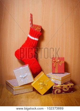 Winter Warm Sock With Christmas Gifts On Wooden Background