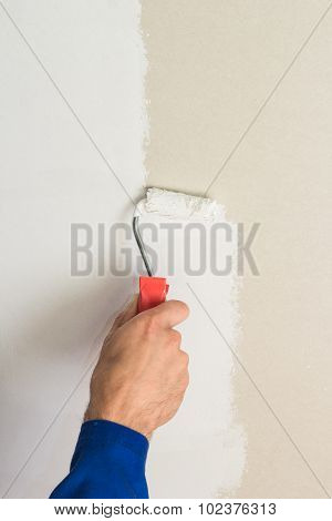 Man using paint roller on the wall