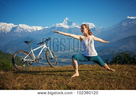 woman practicing yoga relaxing after riding bikes high in mountain