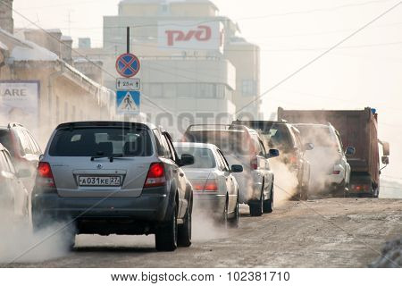 Khabarovsk, Russia - January 5, 2011: Cars Moving On Ice Winter Road Spreading Exhaust