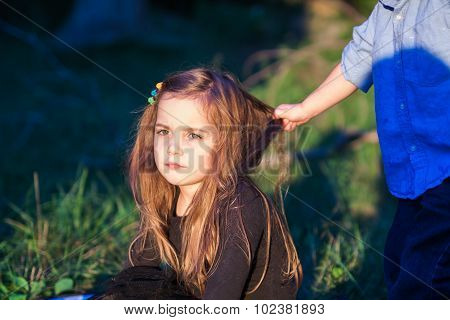 Portrait Of A Beautiful Little Girl While Her Toddler Brother Is Pulling Her Hair