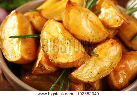 Baked potato wedges in bowl, closeup