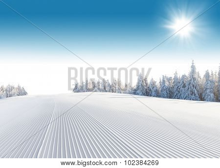 Winter snowy forest with slope and blue sky