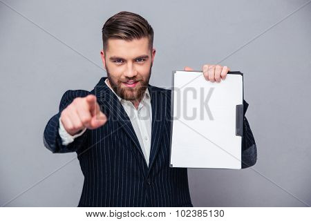 Portrait of a businessman showing blank clipboard and showing finger at camera over gray background
