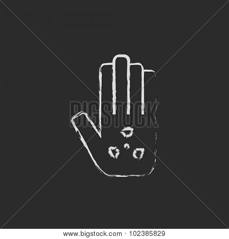 Ionizing radiation sign on a palm hand drawn in chalk on a blackboard vector white icon isolated on a black background.